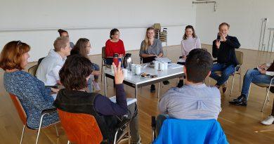 Das Bild zeigt Jugendliche, die in einem Kreis sitzen.