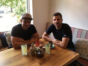 """Das Bild zeigt Armin Wurm mit einem Freund bei einm Kaffee in der Brasserie """"Heimlich""""."""