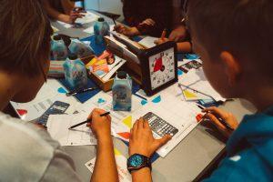 Das Bild zeigt eine Gruppe von Jugendlichen, die gemeinsam an digitalen Projekten arbeiten.