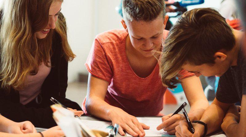 Das Bild zeigt drei Jugendliche, die als Gruppe etwas erarbeiten.