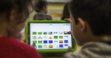 Das Bild zeigt zwei Kinder, die an einem Tablet arbeiten