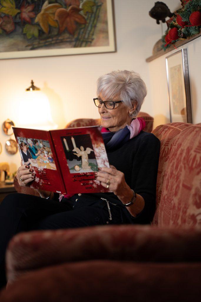 Frau Fehrmann schaut in ein Fotoalbum.