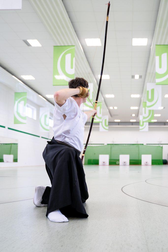 Kyudo Mann mit angespannten Bogen auf Zielscheibe gerichtet