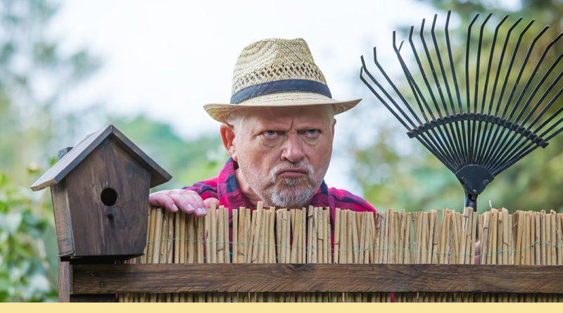 Einer der Nachbarn guckt grimmig mit einem Rechen in der Hand über den Gartenzaun