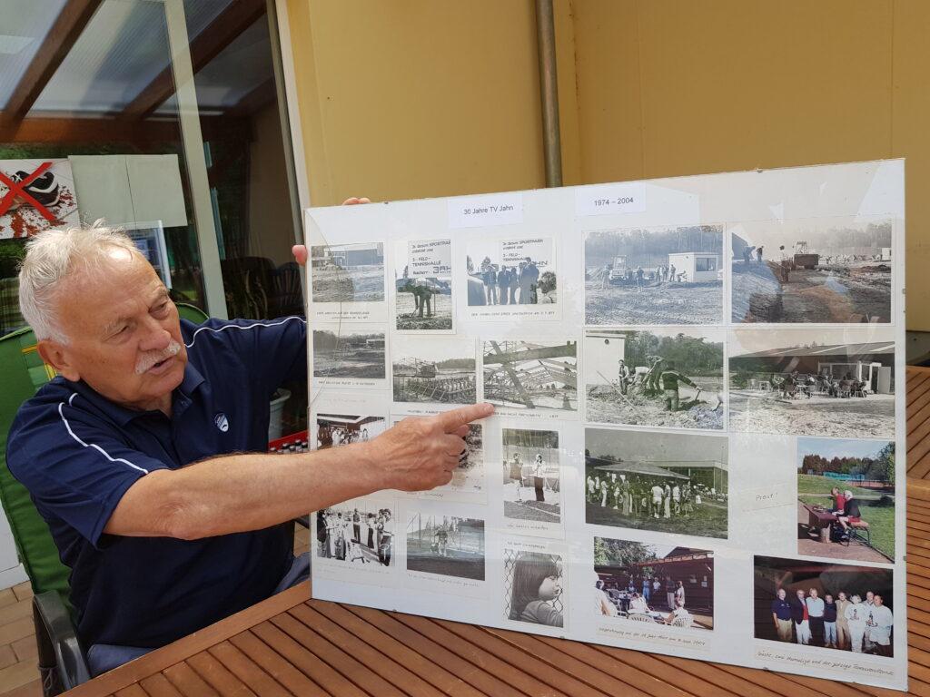 1. Vorsitzende Günther Schultz zeigt alte Fotos vom Brand auf dem Tennisgelände